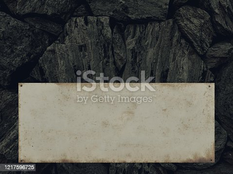 Natural stone wall with metal shield, copy space - structures as background.