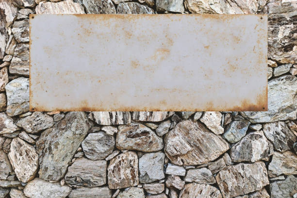 Natural stone wall with metal shield, copy space stock photo