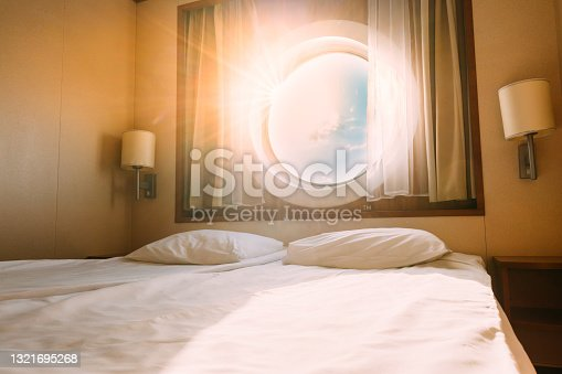istock Natural Sunlight Shining Through Ship Window In Craft Cabin With Bed. View On Sea. Luxury Cabin On Ferry Boat Or Cruise Liner. Sea Cruise Vacation Trip Travel Concept 1321695268