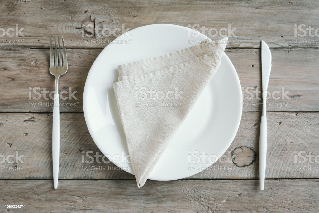 Empty table setting - plain white ceramic plate, cutlery on wooden...