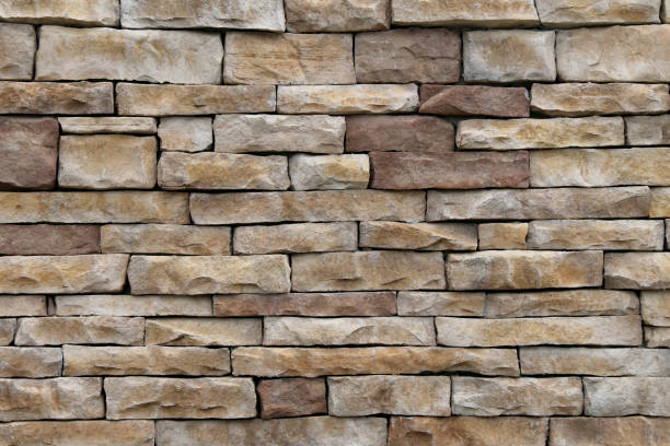 natural tan and brown thin cut stacked stone block wall with shadows and straight lines suitable for website background marketing backgrounds backdrops architecture architectural layout design stock photo