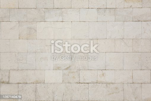 Natural texture and background. The wall of the house is covered with white marble tiles.