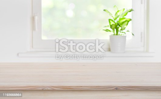 885452818 istock photo Natural texture wooden tabletop with blurred window for product display 1193666864