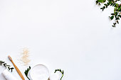 White background with twigs, toothpowder, toothpaste tube and toothbrush in the corners symbolizing herbal toothpastes