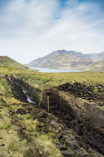 Natural turf moor landscape showing bog cut out for domestic peat usage photographed in Connemara, County Galway, Ireland stock photo