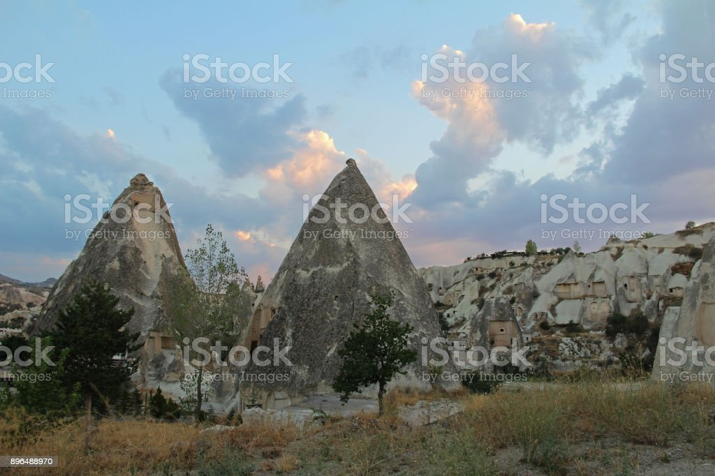 Natural valley with volcanic tuff stone rocks in Goreme in Cappadocia, Turkey, at sunset. stock photo