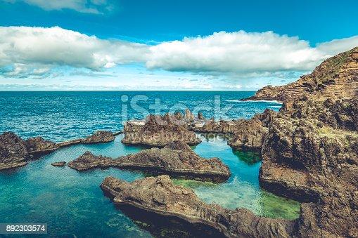 lava rocks natural volcanic pools in porto moniz, madeira island, portugal.