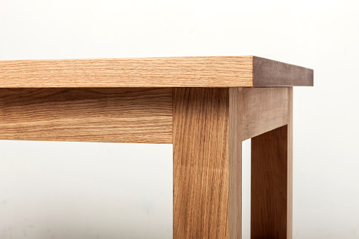 A natural wood(oak) table(desk) corner close up with white background.