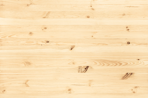 Natural light colored wood texture background viewed from above. Use this clean wooden textured material as graphic design asset for a wall, floor boards, wallpaper, table surface or other furniture.