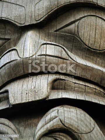 Close up on a natural wood totem pole in the Pacific Northwest.