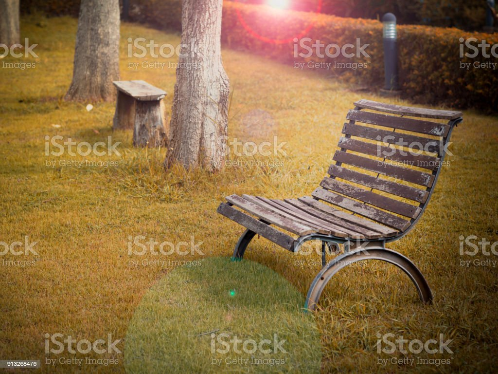 Natural wooden bench or chair on backyard grass with beautiful sunrise or sunset background stock photo