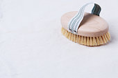 istock Natural wooden brush for dry body brushing on a beige organic cotton fabric 1211647223