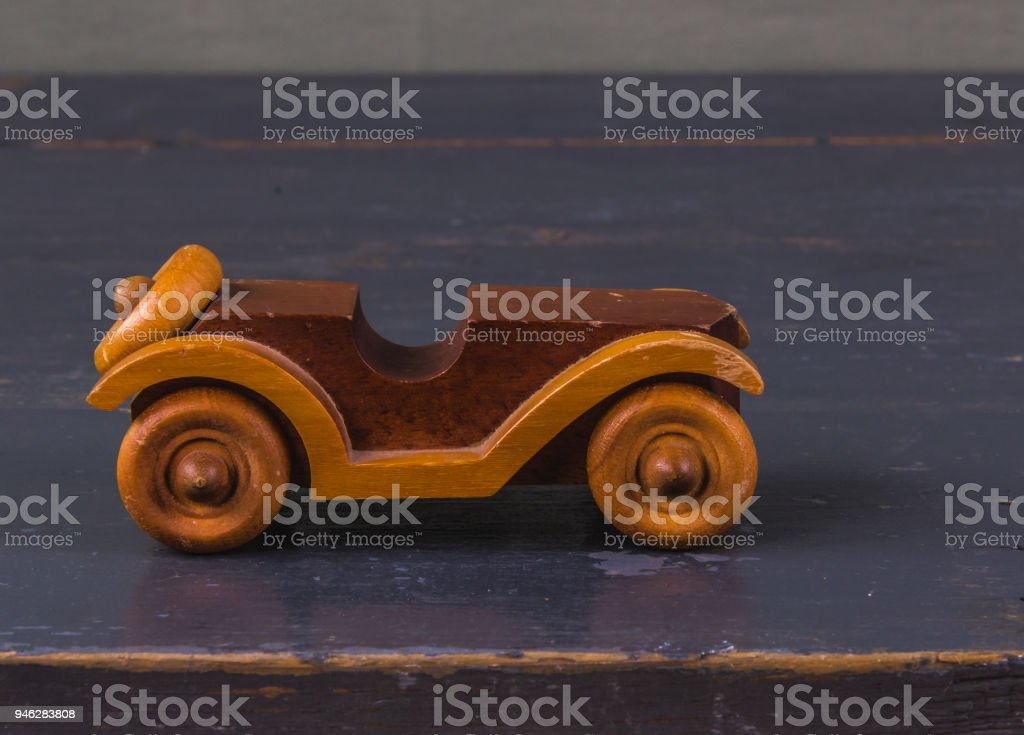 Natural wooden old car toy on the wooden gray background, vintag stock photo