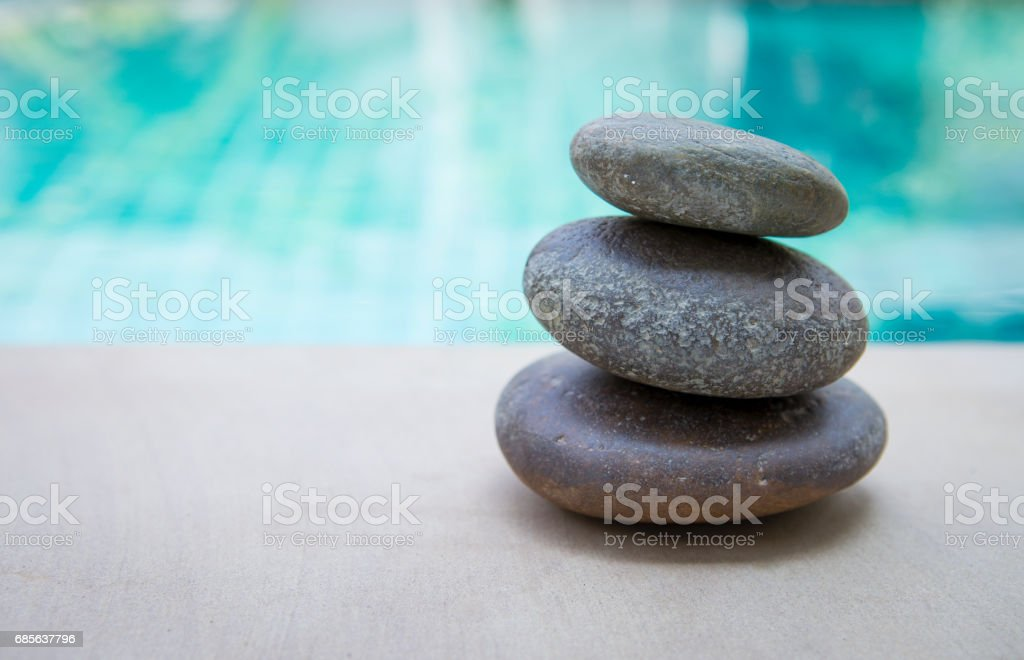 Natural Zen stone stack over blurred blue swimming pool background 免版稅 stock photo