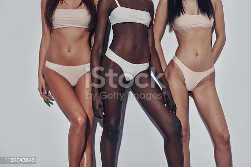Close up of three attractive mixed race women in lingerie standing against grey background