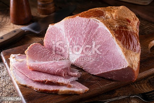 A delicious naturally smoked ham on a rustic wood cutting board.