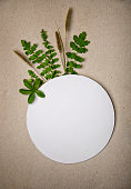 Green leaves and wild grass arranged around white circle paper template empty for your text, on a cardboard paper as a background.