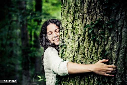 Pretty natural girl with black curled hair leaning on a tree trunk in a beautiful lush green forest