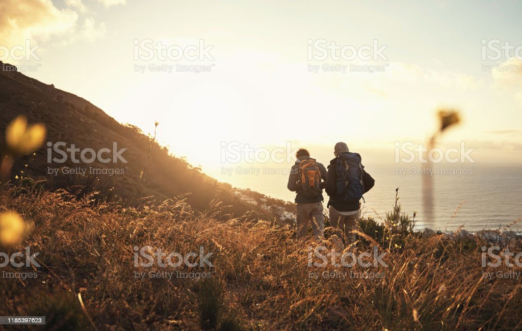 Nature gives you a reason to never be bored again Shot of a couple going for a hike up the mountain Active Lifestyle Stock Photo