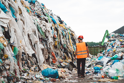 A worker walking between the heaps of garbage