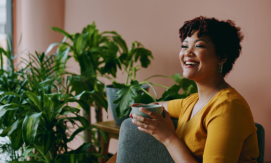Shot of a young woman drinking coffee while relaxing with plants around her at home
