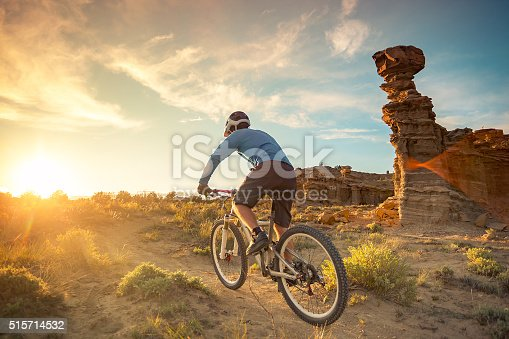 a man pedals his mountain bike while cycling in solitude.  the sunshine creates a lens flare in the desert landscape.  horizontal wide angle composition with copy space.   gallup, new mexico.