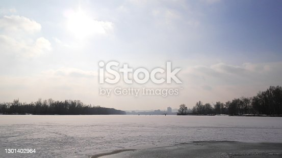 Nature photo winter. Frozen river, blue sky, sun in the sky, ice.