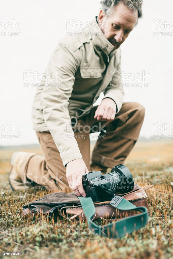 Nature photographer in field picking up camera. stock photo