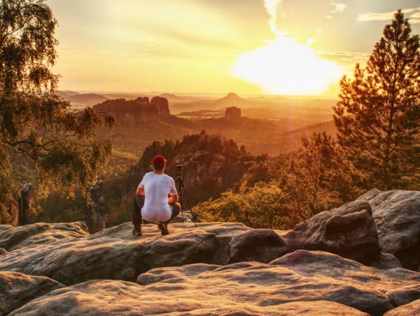 Nature photographer takes photos on peak of rock. stock photo