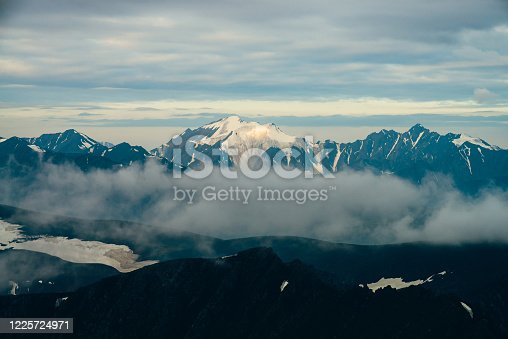 Atmospheric alpine landscape with big snowy mountains among low clouds in golden hour. Wonderful highland scenery with massive glacier on giant mountain range in sunrise. Shiny snow on big rockies.