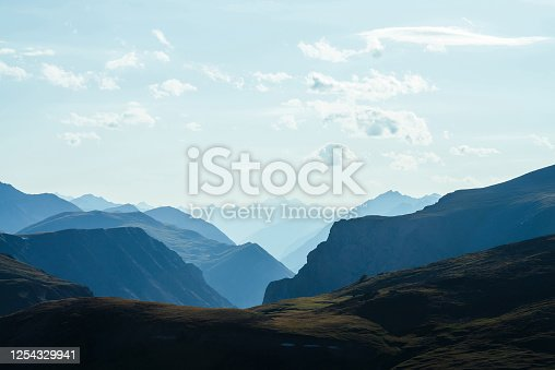 Awesome aerial view to great mountains in distance behind deep gorge. Scenic mountain landscape with giant rockies and deep abyss. Wonderful highland scenery with huge cliff. Big rocks and precipice.