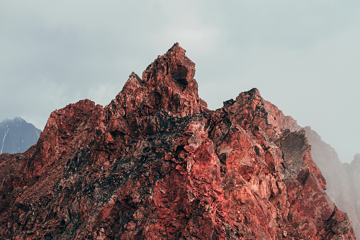 Surreal pointed rocky pinnacle in cloudy sky. Vivid big pointy rocky peak. Giant piece of stone. Atmospheric minimalist alpine landscape. Sharp rocky mountain top in sky. Wonderful highland scenery.
