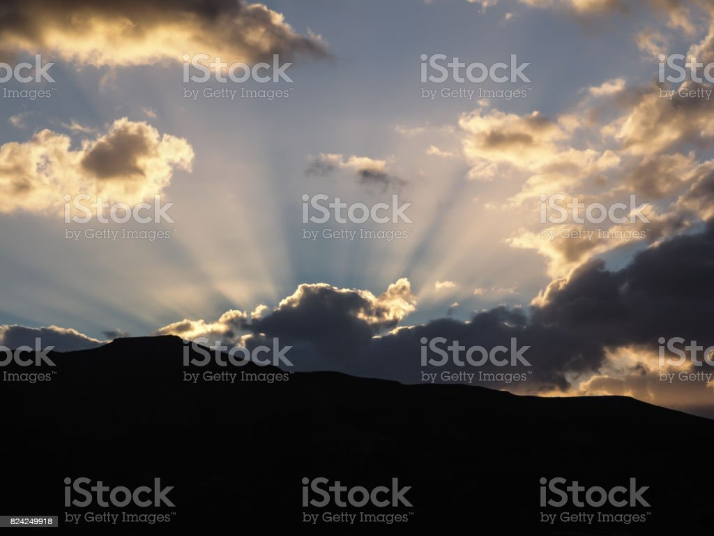 Nature spactacle with clouds behind a mountain at twilight stock photo