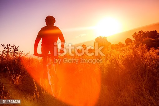 man riding mountain bike silhouetted against sunshine lens flare while riding in the desert landscape of the sandia mountains.  horizontal composition.