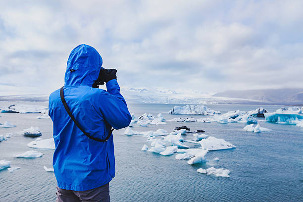 nature travel photographer taking photos in Iceland nature travel photographer, person taking photo of arctic icebergs in Iceland jokulsarlon stock pictures, royalty-free photos & images