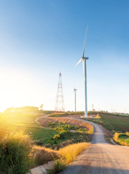 Nature wind turbines and solar panels with high voltage electricity power line for clean energy in mountains stock photo