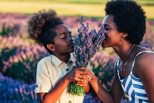 Afro mother and her daughter bonding together outdoors at the lavender field