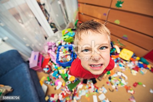 Portrait of a naughty and messy little boy. The boy looks angrily at the camera.