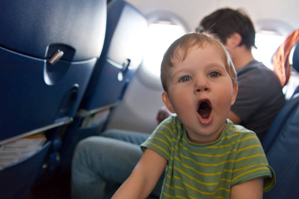 Naughty boy travelling by plane Mischief child in plane inconvenience stock pictures, royalty-free photos & images