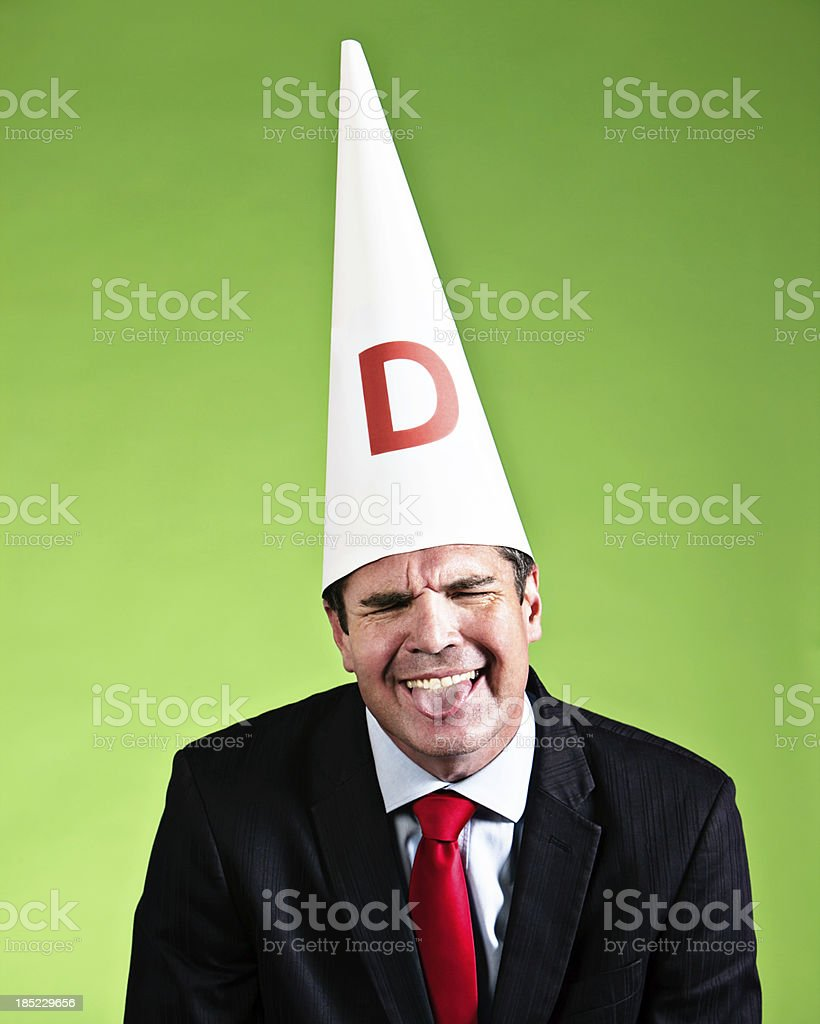 Naughty businessman grimaces in dunce cap sticking out tongue stock photo