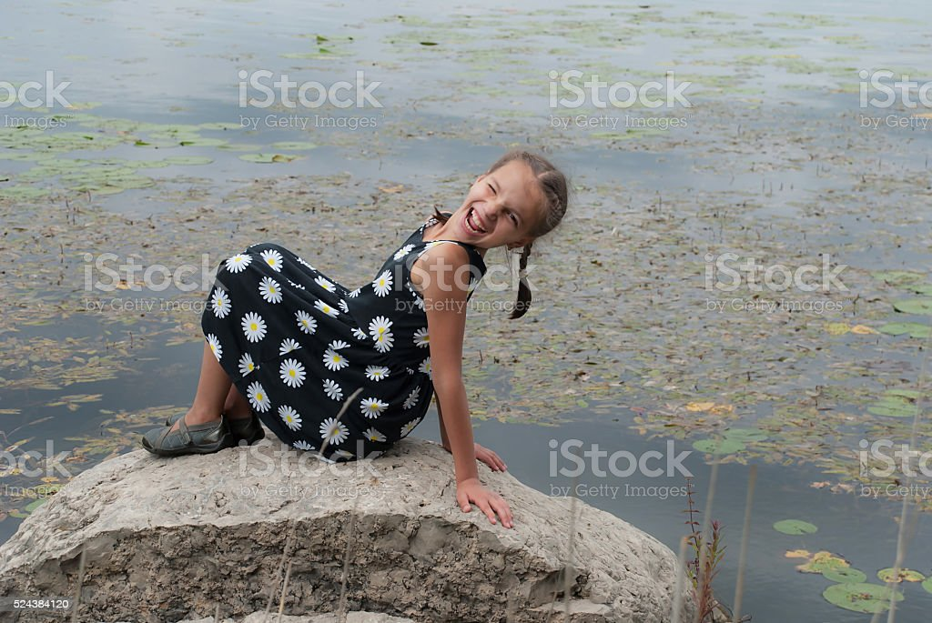 Naughty girl is on a rock near the lake stock photo