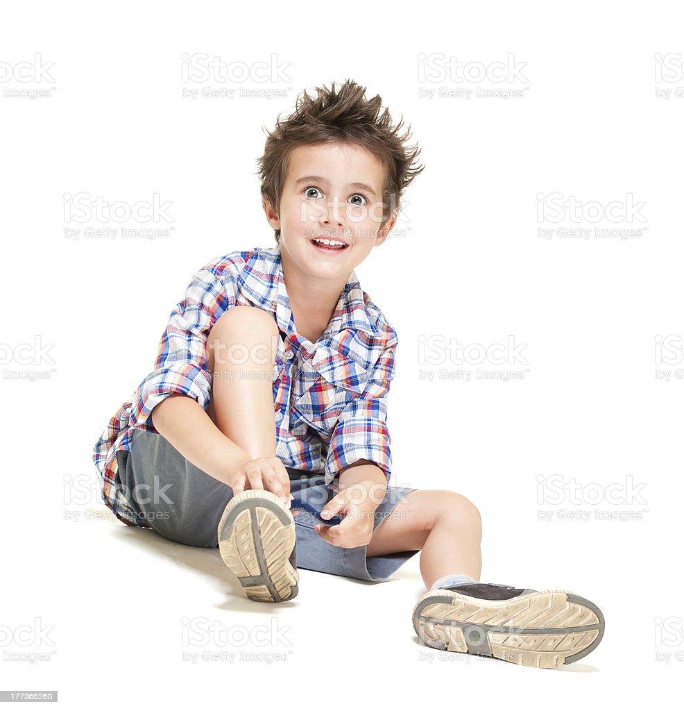 Frech Behaart kleine Junge in shorts und T-shirt putting-Schuh – Foto