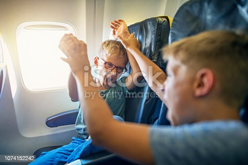 Two naughty boys travelling by plane. The boys are fighting and yelling. Naughty kids are a nightmare for their parents and other passengers. Nikon D850