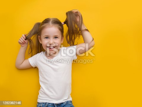 A naughty little girl in a white T-shirt is holding herself by the hair on a yellow background. Mocap. Copyspace