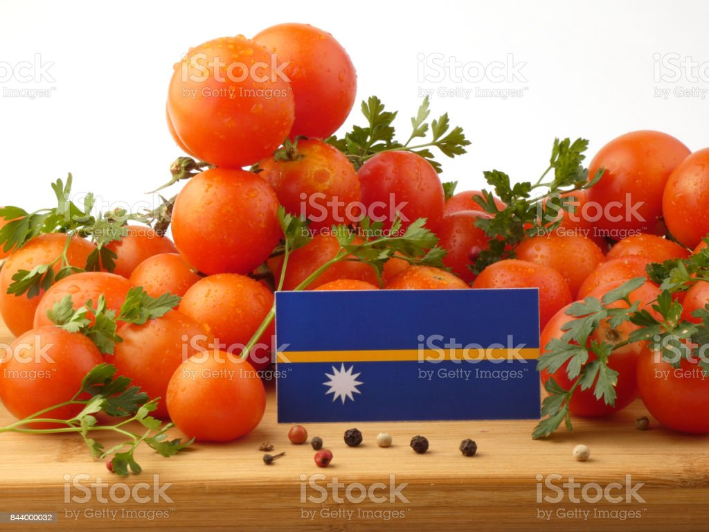 Nauru flag on a wooden panel with tomatoes isolated on a white background stock photo