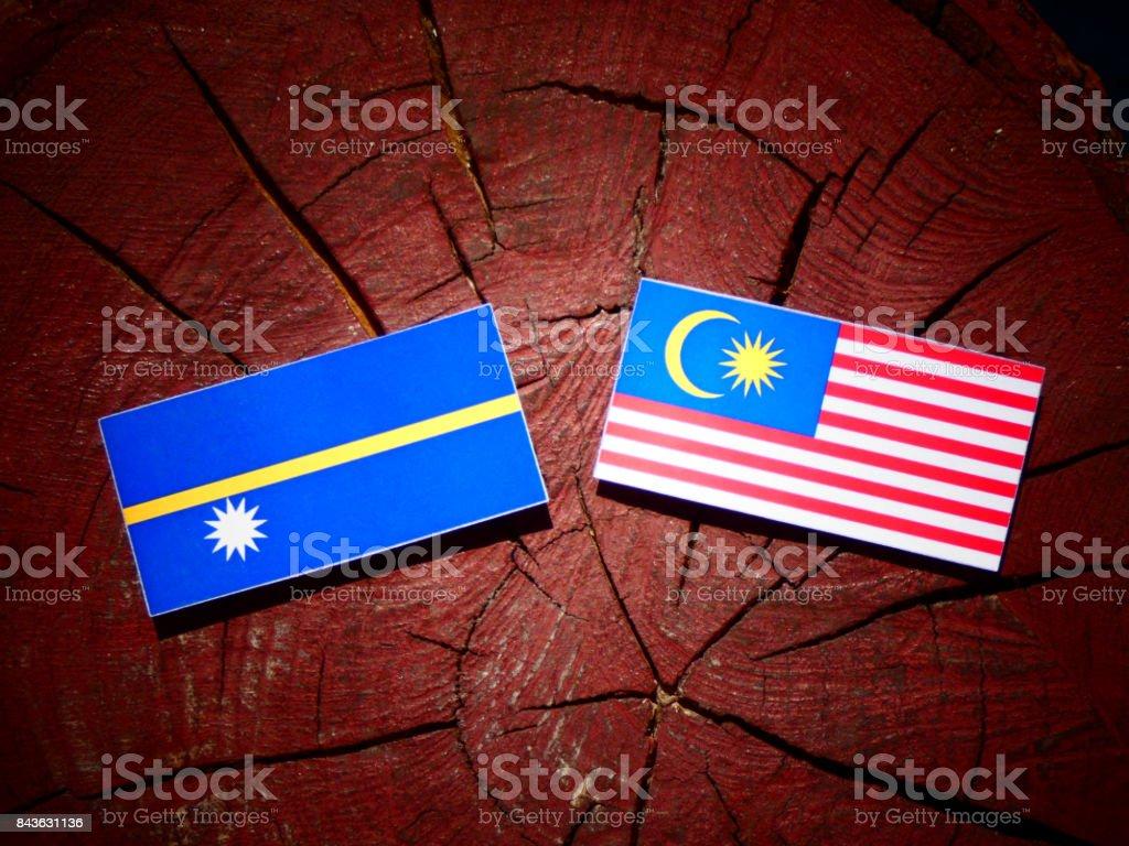 Nauru flag with Malaysian flag on a tree stump isolated stock photo