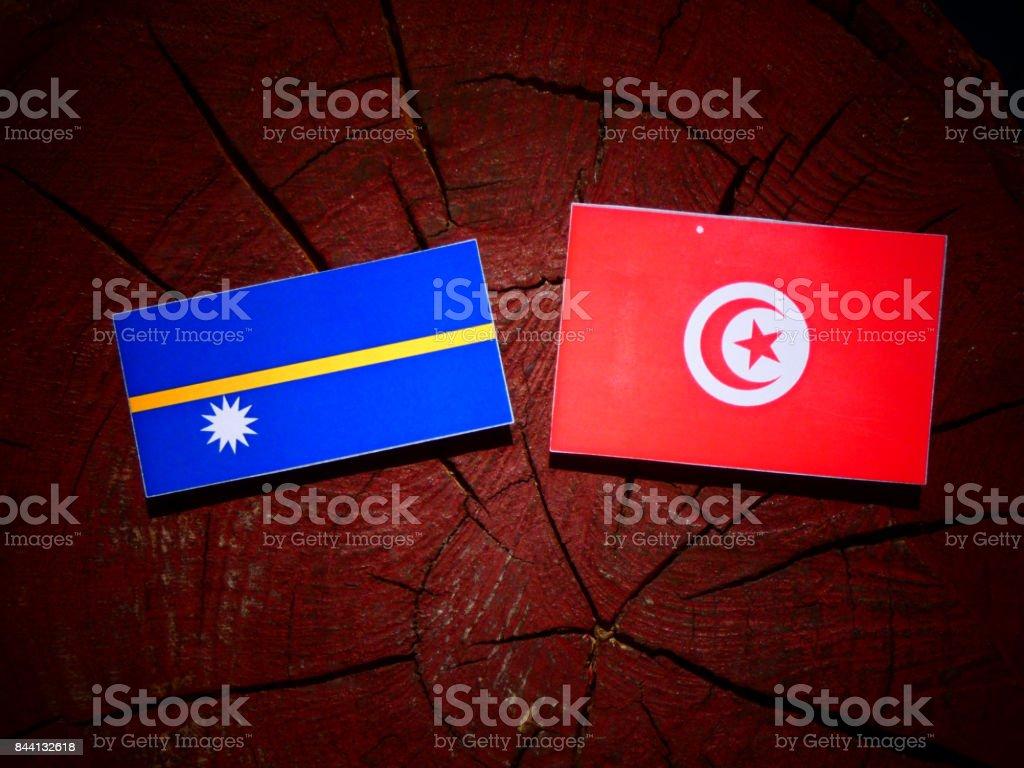Nauru flag with Tunisian flag on a tree stump isolated stock photo