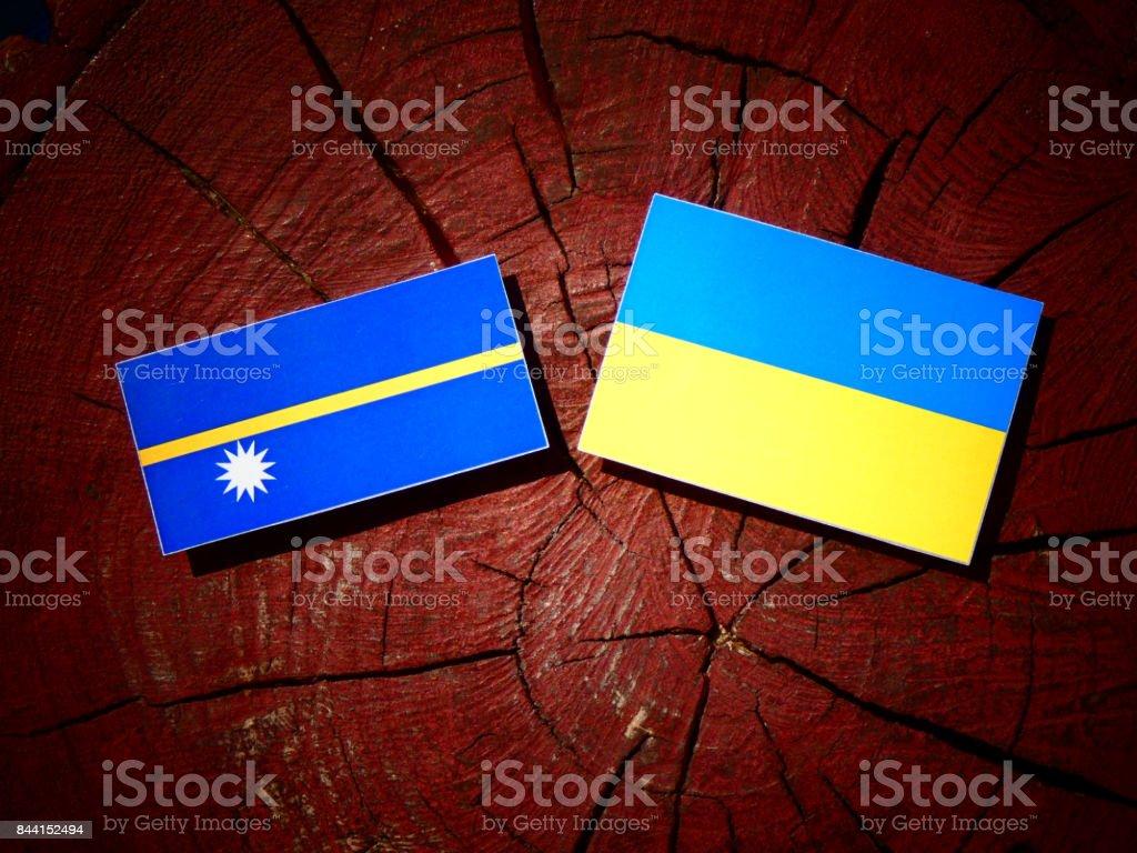 Nauru flag with Ukrainian flag on a tree stump isolated stock photo