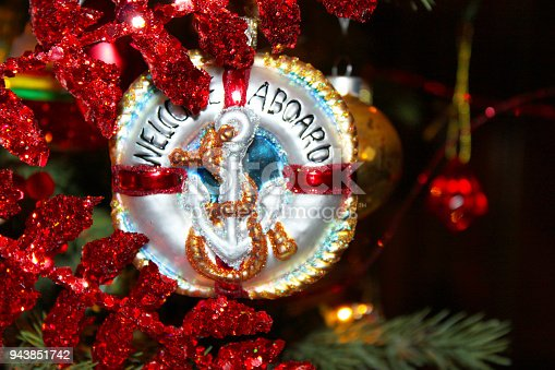 istock Nautical Christmas Ornament with anchor that says Welcome Aboard on Chistmas tree with red glitter leaves around it 943851742