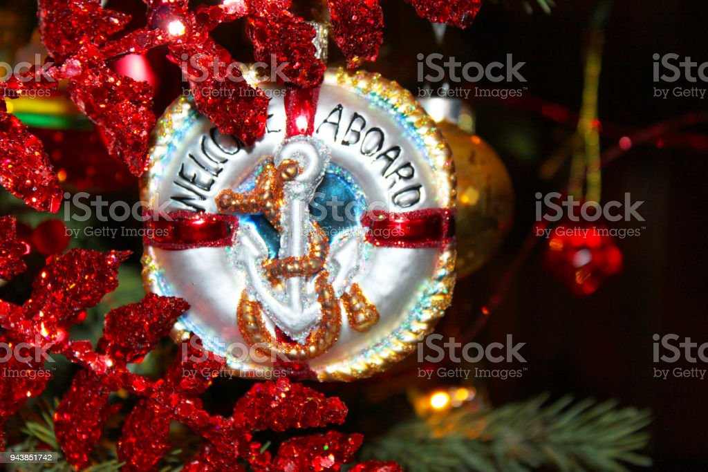 Nautical Christmas Ornament with anchor that says Welcome Aboard on Chistmas tree with red glitter leaves around it stock photo